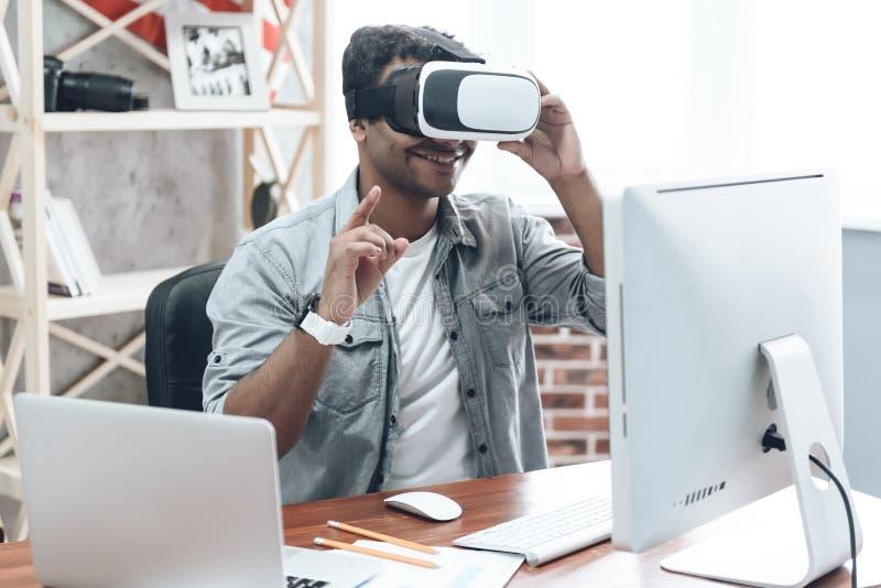 Glücklicher indischer junger Mann zu Hause in VR-Gläsern lizenzfreie stockfotos