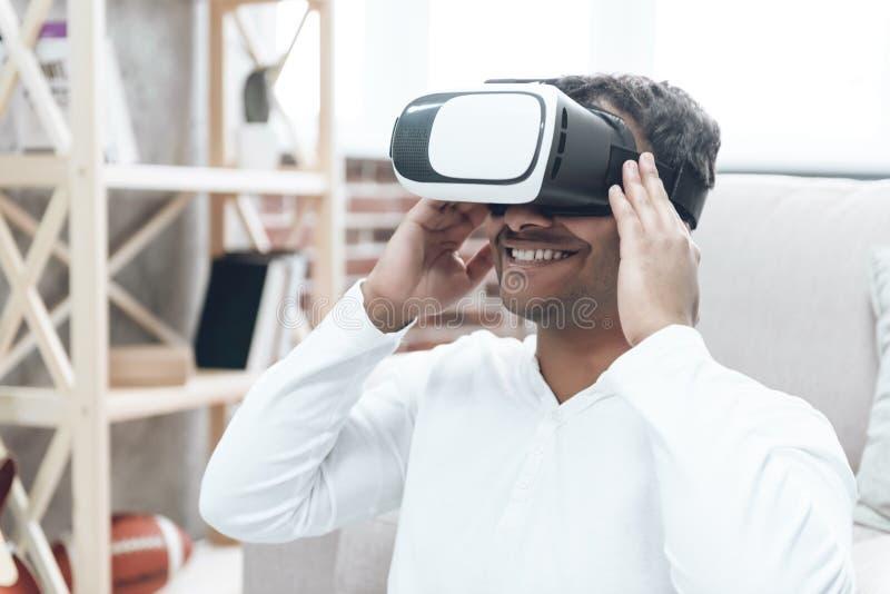Glücklicher indischer junger Mann zu Hause in VR-Gläsern stockfotos