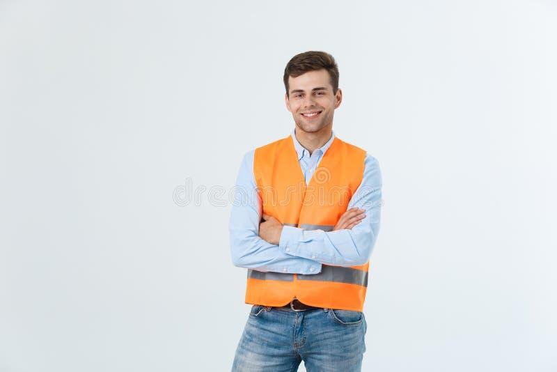 Glücklicher Ingenieur, der sicher lächeln und stehen, Kerl tragendes caro Hemd und Jeans mit orange Weste, auf Weiß stockfotografie