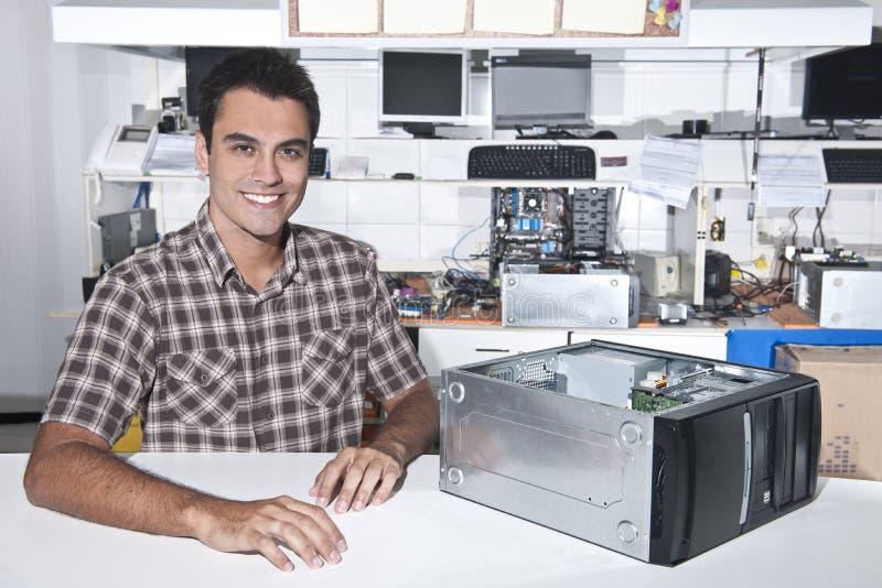 Glücklicher Inhaber eines Computerreparaturspeichers lizenzfreie stockfotografie