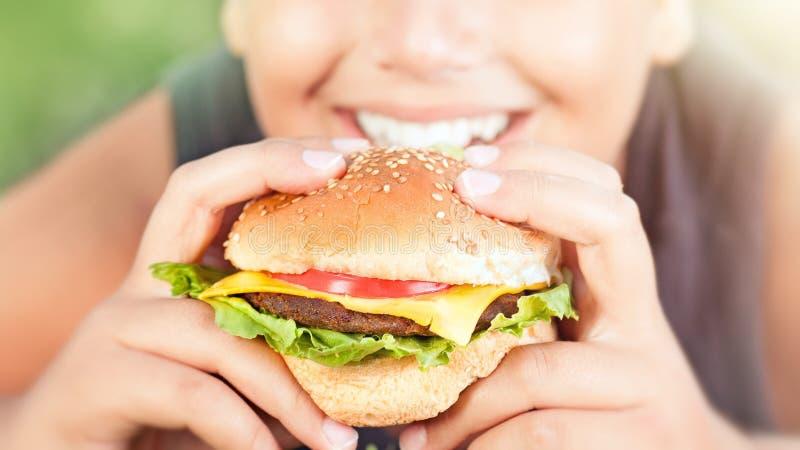 Glücklicher jugendlich Junge, der Burger isst stockbild