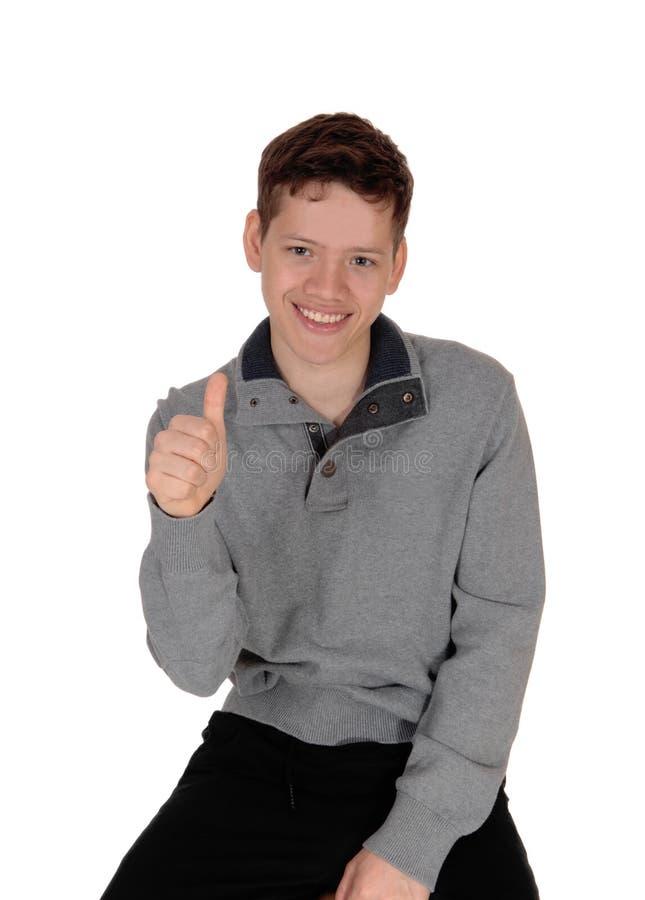 Glücklicher jugendlich Junge, der sich seinen Daumen zeigt stockfoto