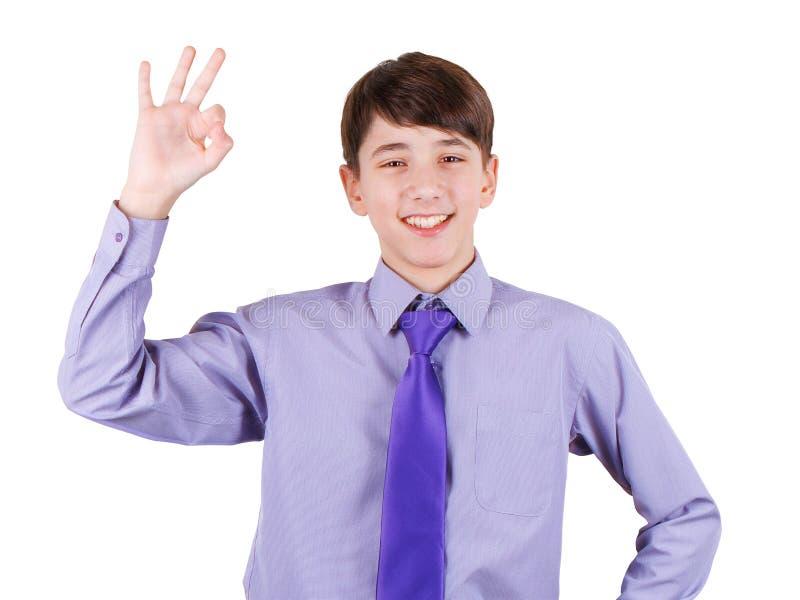 Glücklicher jugendlich Junge im Hemd und Bindung, die OKAYzeichen und das Lächeln lokalisiert auf Weiß gestikulieren lizenzfreies stockbild
