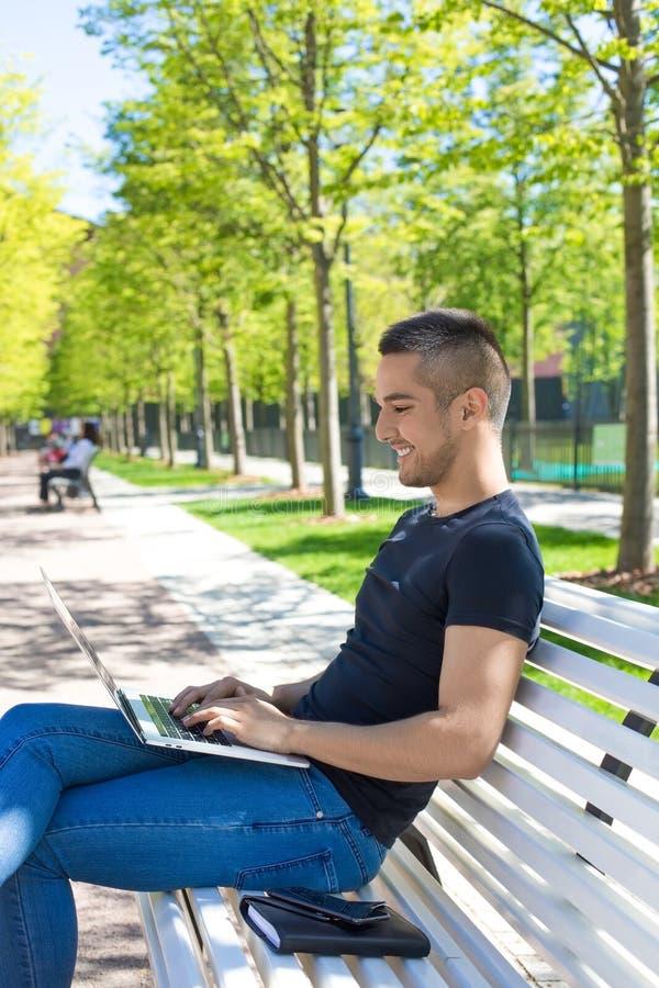 Glücklicher Jugendlicher, der an netbook beim Stillstehen im Park am sonnigen Sommertag arbeitet Mann unter Verwendung der Anwend stockfotografie