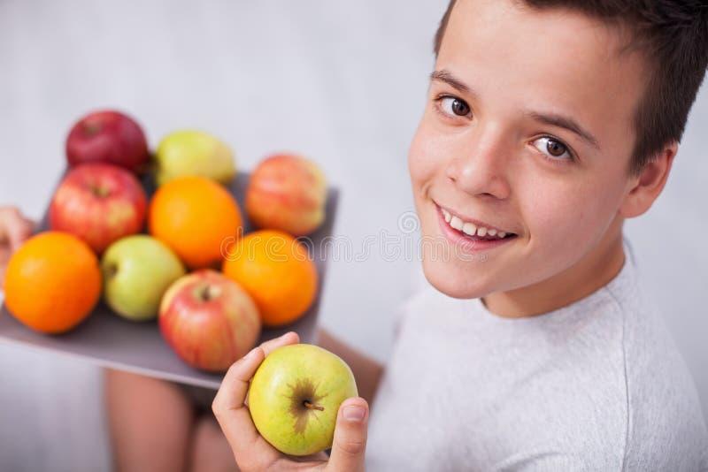 Glücklicher Jugendlichjunge, der eine Platte von frischen Früchten hält lizenzfreies stockbild