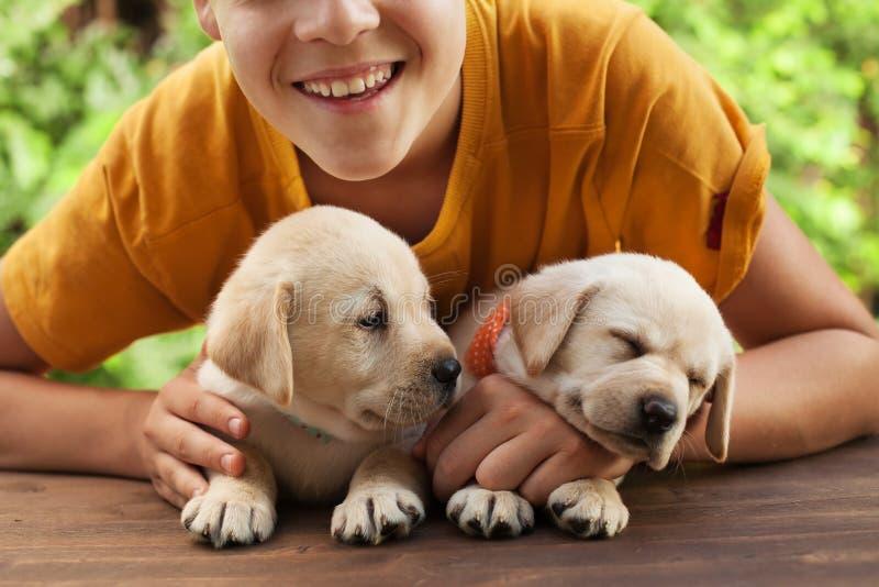 Glücklicher Jugendlichjunge, der mit seinen netten Labrador-Welpen aufwirft stockfotografie