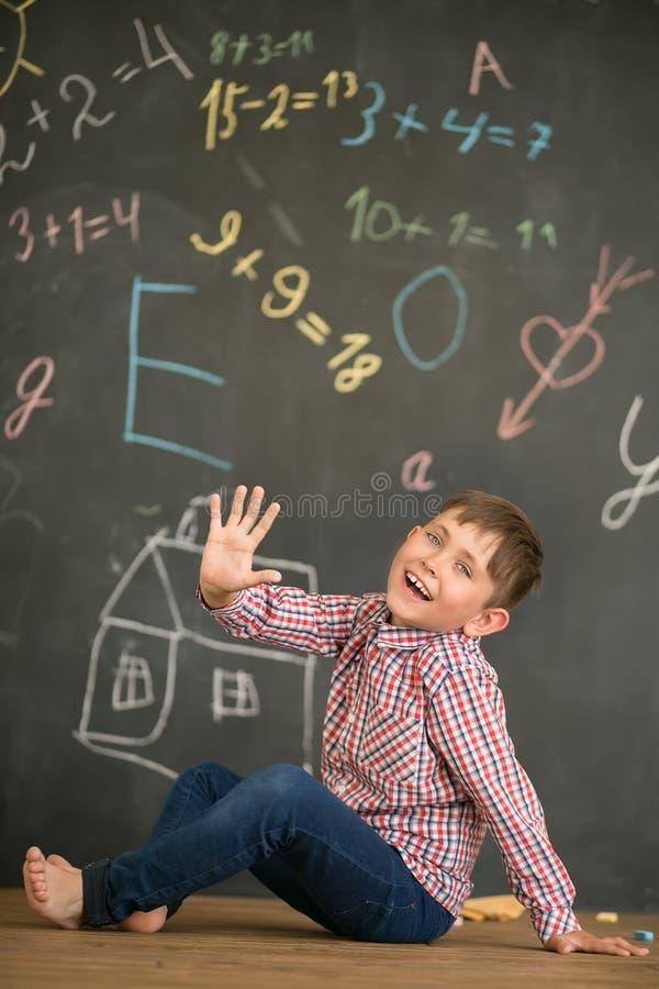 Glücklicher Junge auf dem Hintergrund einer Schulbehörde, die fünf Finger zeigt stockfotografie
