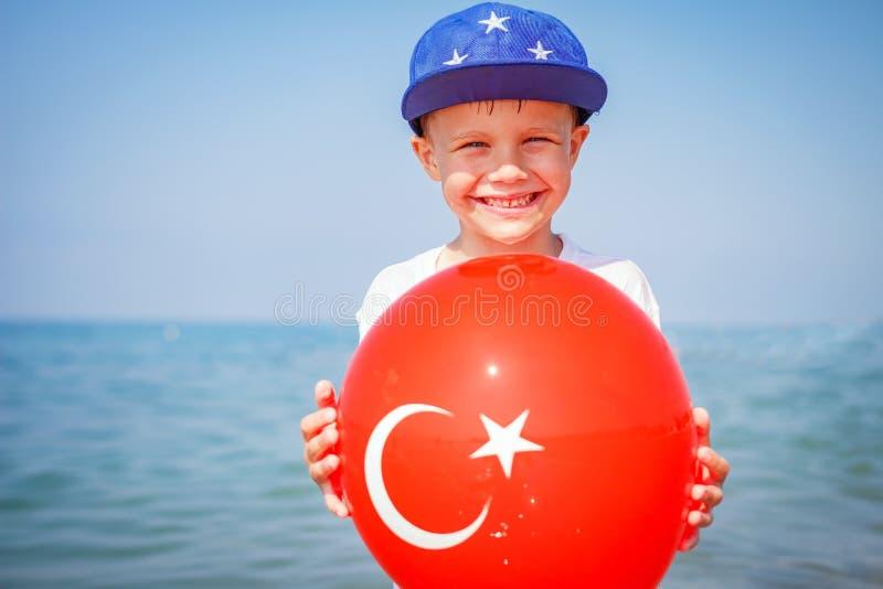 Glücklicher Junge auf Meer, die Türkei Smillings-Kind mit Ballon der türkischen Flagge Feiertag auf Seestrand stockbild