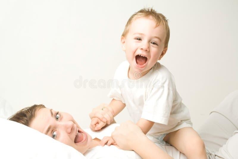 Glücklicher Junge auf Mutter lizenzfreie stockfotos