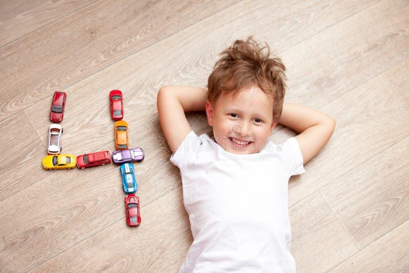 Glücklicher Junge, der auf dem Boden mit Spielwaren spielt stockfoto