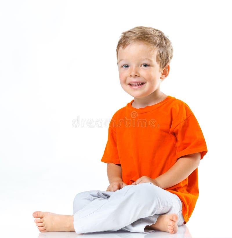 Glücklicher Junge, der auf dem Boden sitzt stockbild