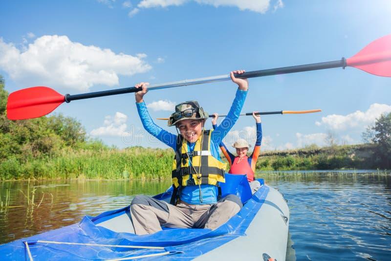 Glücklicher Junge, der auf dem Fluss an einem sonnigen Tag während der Sommerferien Kayak fährt stockbild