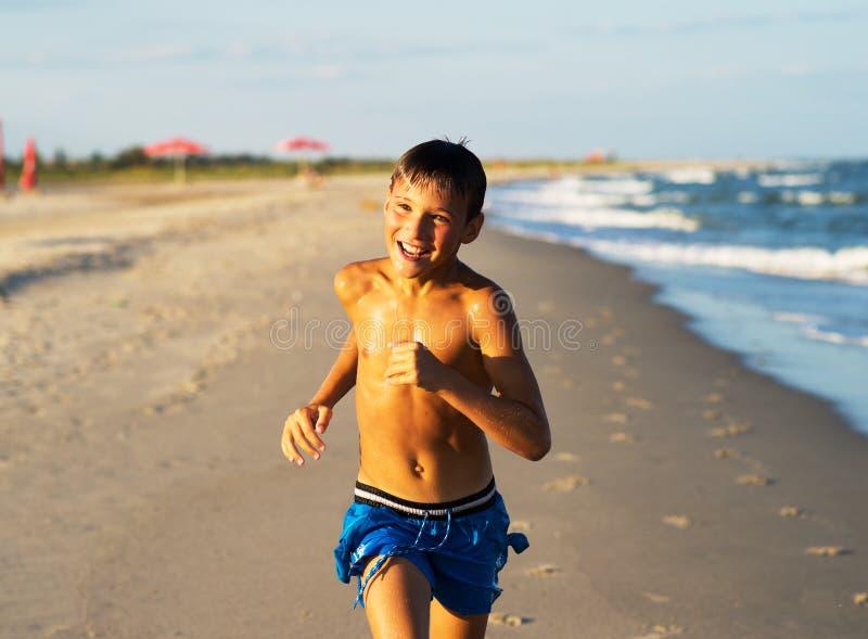 Glücklicher Junge, der auf dem Seestrand am Sommer läuft stockbild