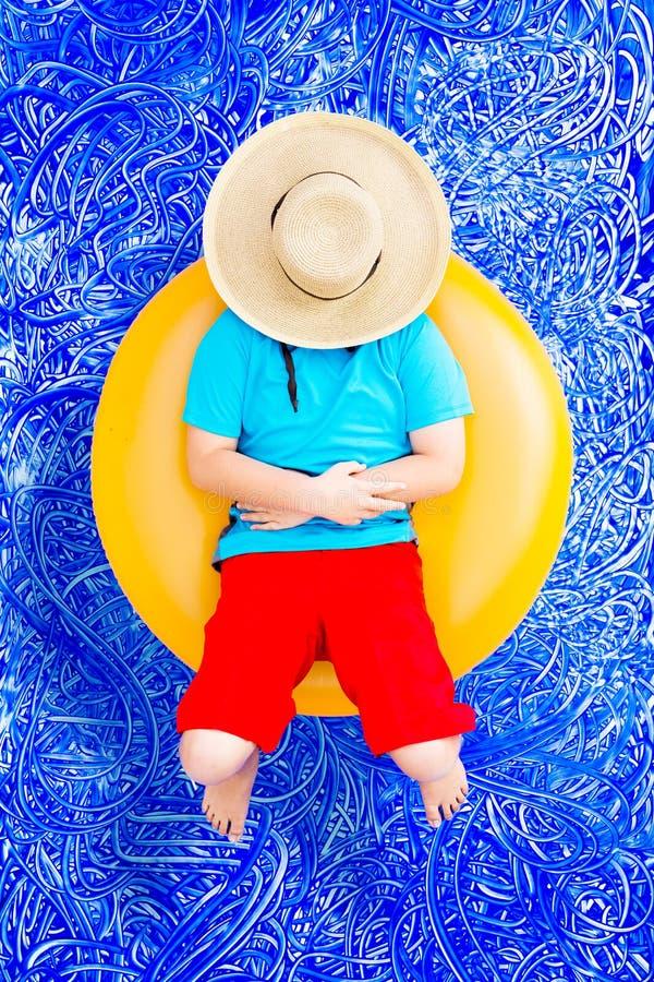 Glücklicher Junge, der auf einem Rohr im Pool sich entspannt stockbild