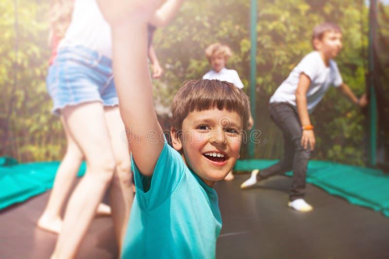 Glücklicher Junge, der auf Trampoline mit seinen Freunden springt lizenzfreies stockbild