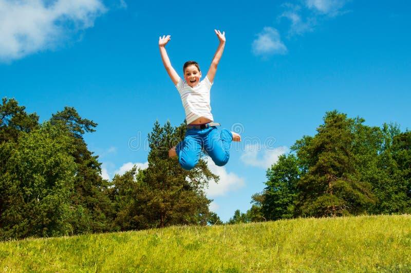 Glücklicher Junge, der draußen springt lizenzfreies stockfoto