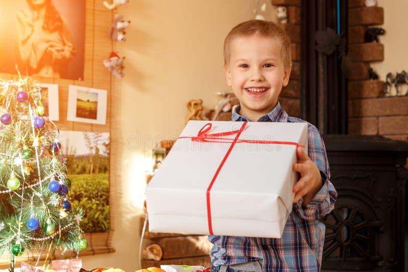 Glücklicher Junge, der ein Geschenk für das neue Jahr hält stockbilder