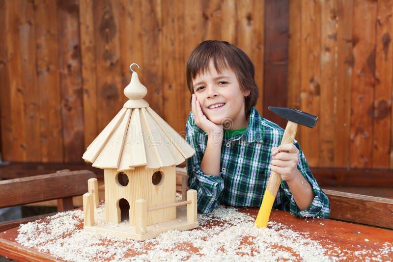 Glücklicher Junge, der ein Vogelhaus für Winterzeit errichtet lizenzfreie stockfotos