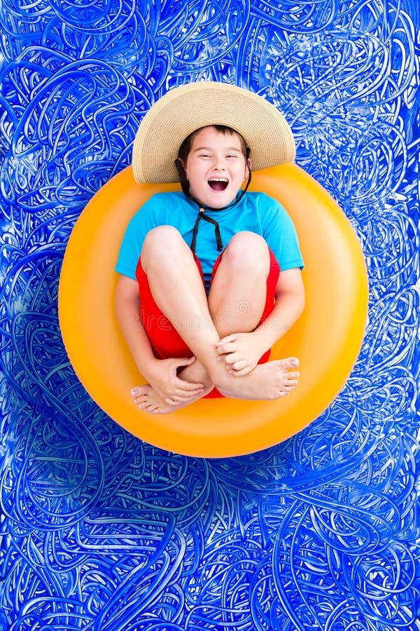Glücklicher Junge, der in einem Sommerpool sich entspannt lizenzfreie stockfotografie