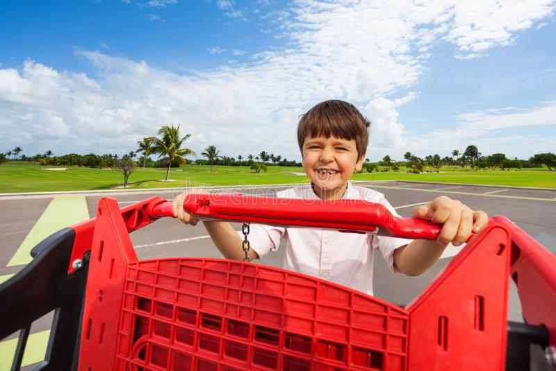 Gl?cklicher Junge, der Einkaufswagen am Parkplatz dr?ckt lizenzfreies stockfoto