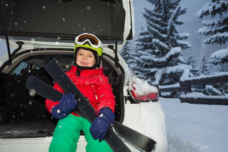Glücklicher Junge, der im Autokofferraum nach Skitour sitzt stockbilder
