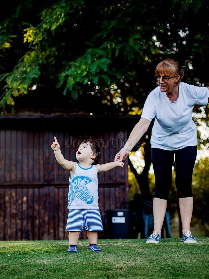 Glücklicher Junge, der lustige Gesichter und Ausdrücke beim Gehen mit seiner Großmutter macht stockfotos