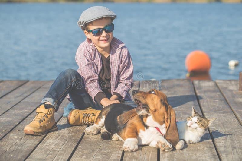 Glücklicher Junge, der mit seinem Hund und Katze durch den Fluss spielt stockfotos