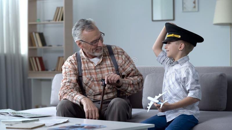 Glücklicher Junge, der mit Spielzeugflugzeug, großväterlicher ehemaliger Pilot stolz auf Enkel spielt lizenzfreies stockfoto