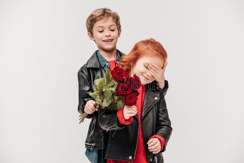 glücklicher Junge, der Rosen Blumenstrauß seiner kleinen Freundin darstellt lizenzfreie stockbilder