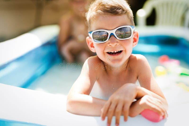 Glücklicher Junge, der Sommerzeit im Swimmingpool genießt lizenzfreie stockfotografie