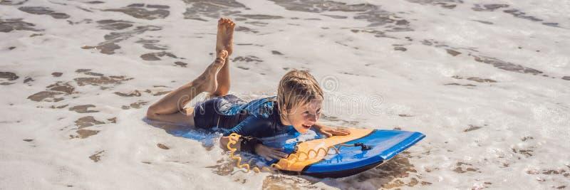 Glücklicher Junge, der Spaß am Strand im Urlaub, mit Boogiebrett FAHNE, LANGES FORMAT hat lizenzfreie stockbilder