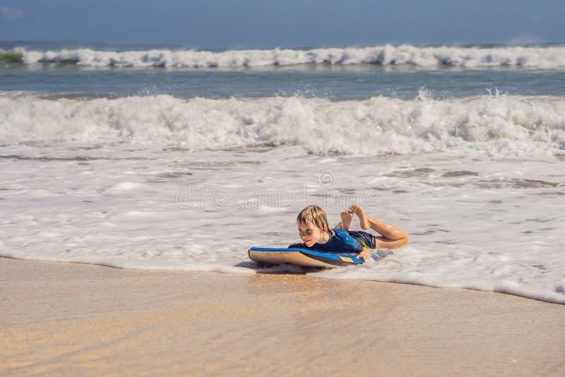 Glücklicher Junge, der Spaß am Strand im Urlaub, mit Boogiebrett hat lizenzfreies stockfoto