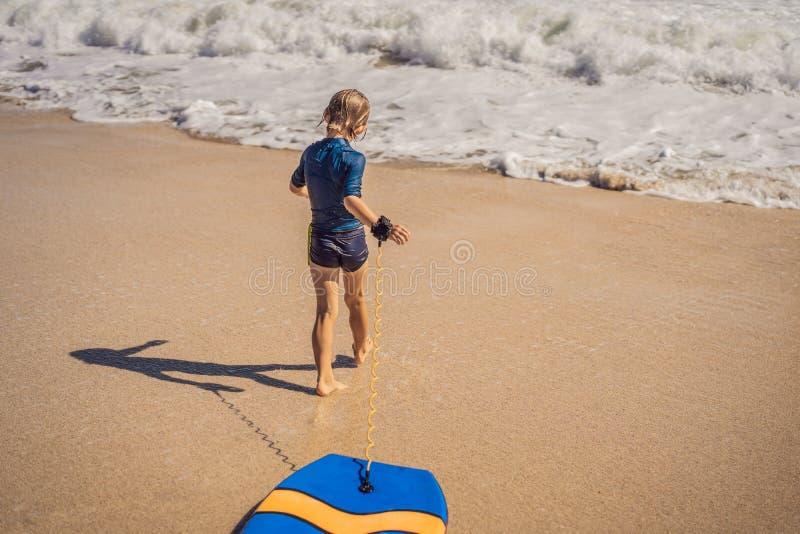 Glücklicher Junge, der Spaß am Strand im Urlaub, mit Boogiebrett hat stockfotos