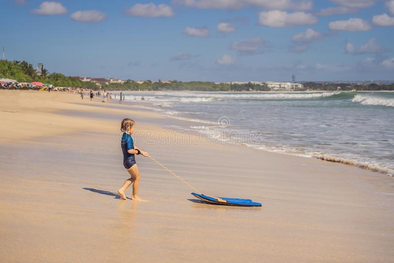 Glücklicher Junge, der Spaß am Strand im Urlaub, mit Boogiebrett hat stockfoto