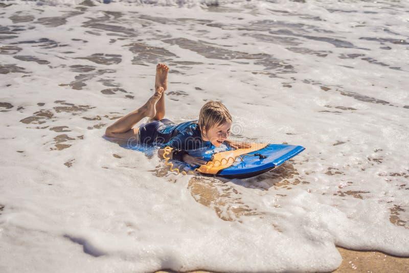 Glücklicher Junge, der Spaß am Strand im Urlaub, mit Boogiebrett hat lizenzfreie stockfotos