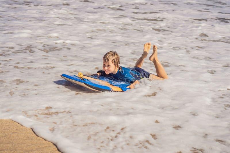 Glücklicher Junge, der Spaß am Strand im Urlaub, mit Boogiebrett hat lizenzfreie stockfotografie