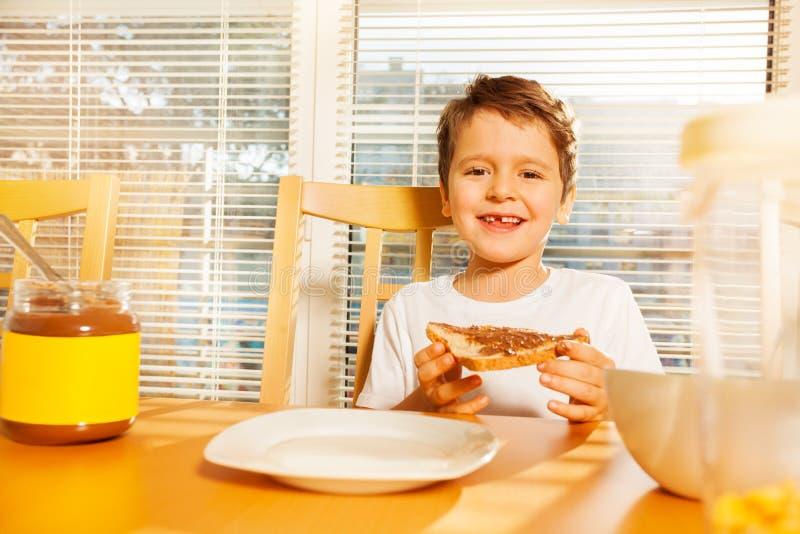 Glücklicher Junge, der Toast mit Schokoladenverbreitung isst stockbild