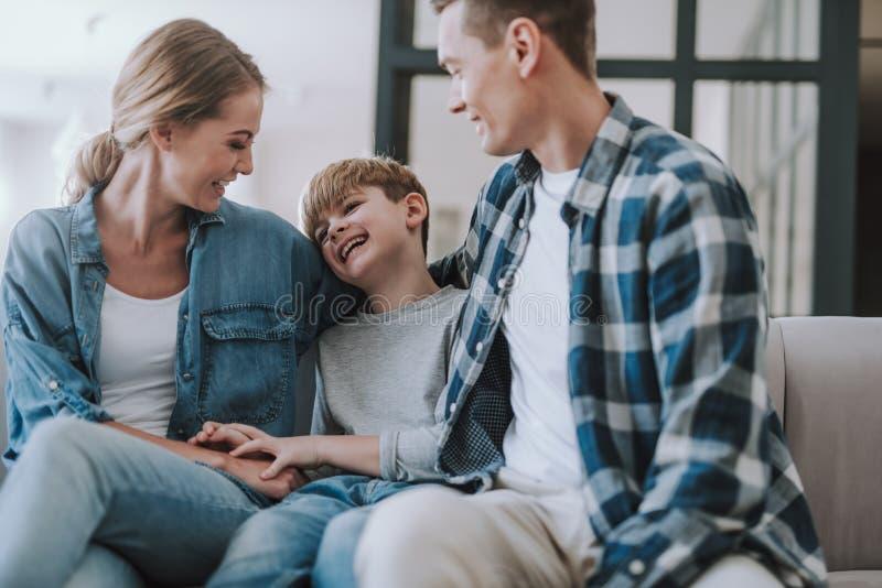 Gl?cklicher Junge, der zwischen seinen Eltern und Lachen sitzt lizenzfreie stockfotografie