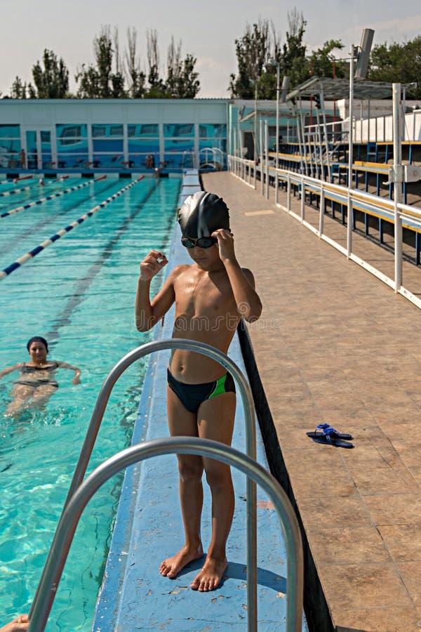 Glücklicher Junge des vertikalen Bildes in der Swimmingpoolstellung lizenzfreie stockfotografie