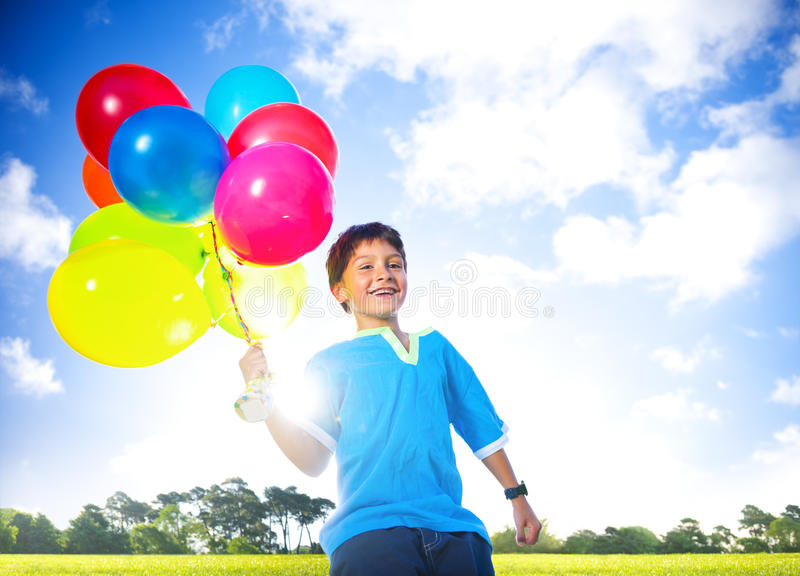 Glücklicher Junge draußen mit A Dutzend von Helium-Ballonen lizenzfreie stockfotos
