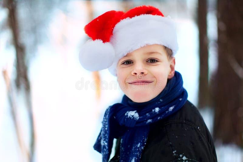Glücklicher Junge in einer Kappe von Santa Claus im Abschluss des Winterwald A lizenzfreie stockfotos