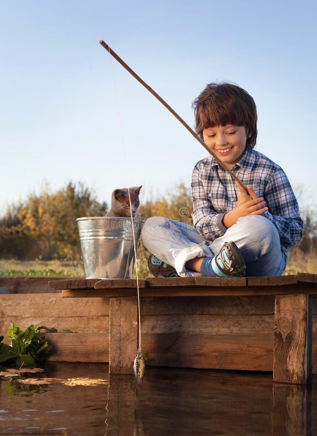 Glücklicher Junge gehen, auf dem Fluss mit Haustier, Kindern eins und Ausrüstung zu fischen stockfotografie