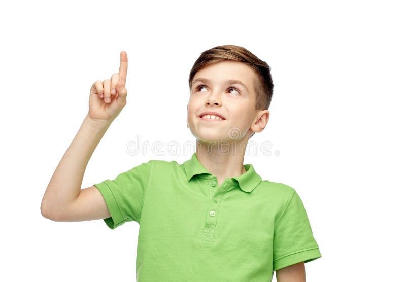 Glücklicher Junge im grünen Polot-shirt Finger oben zeigend stockfoto