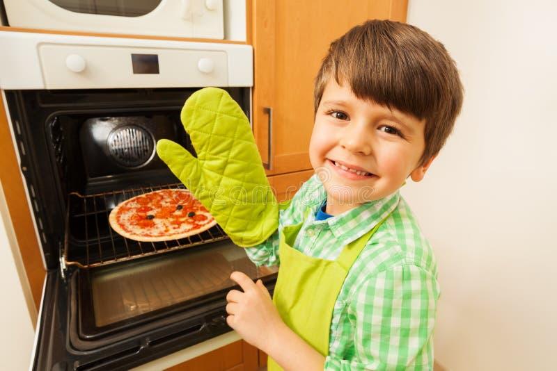 Glücklicher Junge im Handschuh, der heiße Pizza aus Ofen heraus erhält lizenzfreie stockfotografie