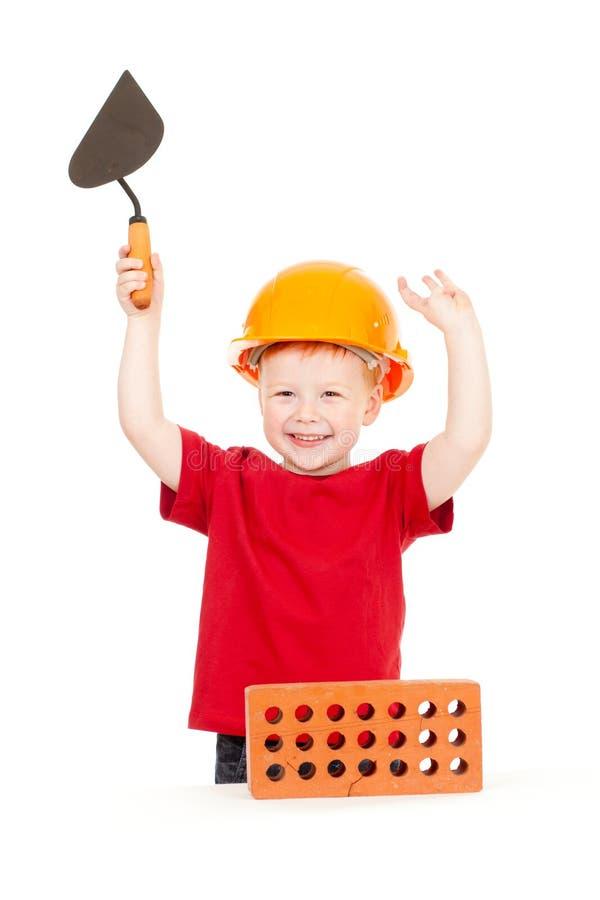 Glücklicher Junge im harten Hut mit Trowel und Ziegelstein stockbild