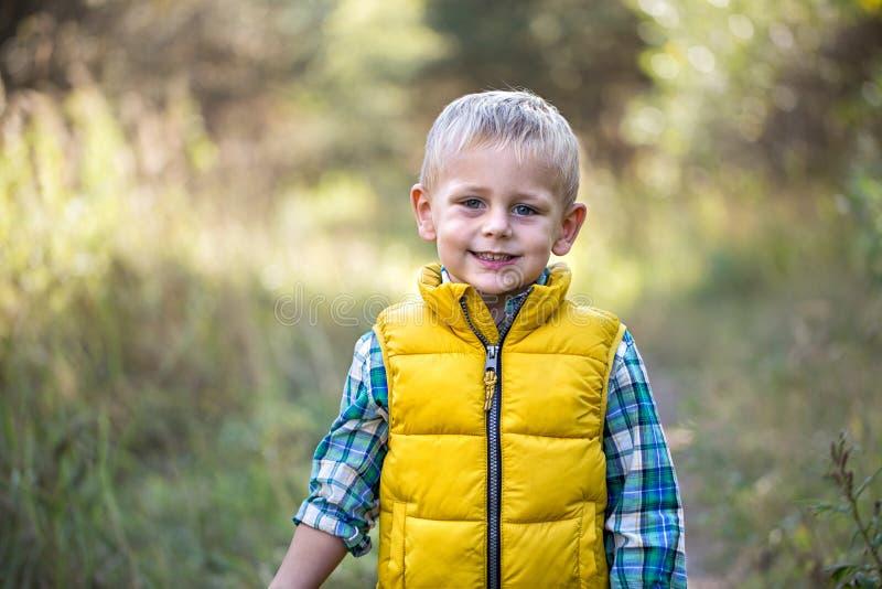 Glücklicher Junge im Wald, der die Kamera betrachtet stockfoto