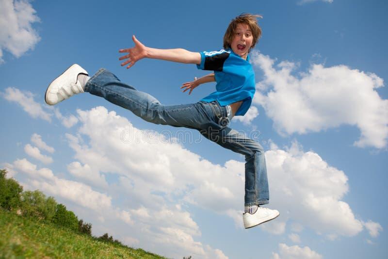 Glücklicher Junge laufen gelassen gegen schönen Himmel stockfotos