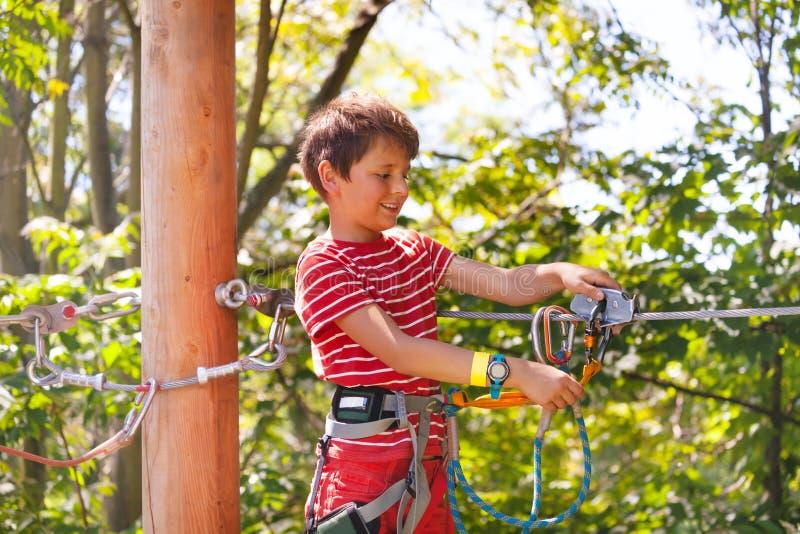 Glücklicher Junge lernen, Ziplinie Laufkatze, Seilpark zu benutzen lizenzfreie stockfotos