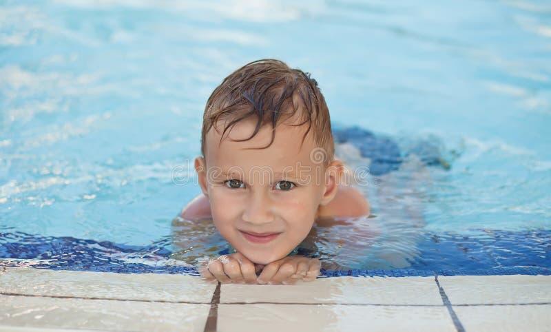 Glücklicher Junge mit dem lächelnden Sitzen des blonden Haares im Swimmingpool stockbild