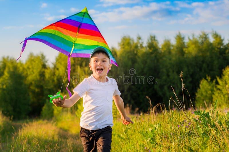 Glücklicher Junge mit einem Drachen, der in eine Wiese im Sommer in der Natur läuft stockbilder